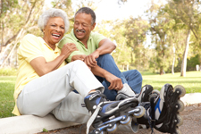 A middle aged couple laughing and smiling at the camera while sitting along a roadway at a park wearing rollerblades