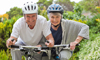 A smiling woman and a man riding their bicycles along wooded trails